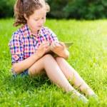 Outdoor ritratto di una ragazza adolescente carina in abiti casual, seduto sull'erba con tavoletta digitale sulle sue ginocchia, lettura e surf — Foto Stock #29132329
