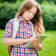 Outdoor portrait of a beautiful teenager girl in casual clothes with backpack holding digital tablet in her hand, typing and reading — Stock Photo #29132337