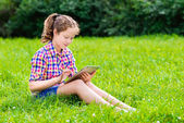 Outdoor portrait of a pretty teenager girl in casual clothes sitting on the grass with digital tablet on her knees, reading and surfing — Stock Photo
