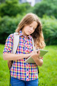 Outdoor portrait of a beautiful teenager girl in casual clothes with backpack holding digital tablet in her hand, typing and reading — Stock Photo