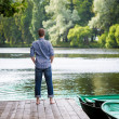 Young handsome man standing on wooden pier, relaxing and meditaing in summer morning, back view — Stock Photo #29241867