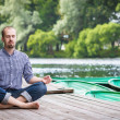 Young handsome bearded man with closed eyes sitting on wooden pier, relaxing and meditating in summer evening — Stock Photo