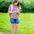 Pretty teenager girl in casual clothes with backpack holding digital tablet in her hand, typing and reading, outdoor portrait — Zdjęcie stockowe #29242123