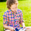 Foto Stock: Beautiful teenager girl sitting on grass and reading book