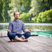 Young handsome bearded man sitting on wooden pier in summer day, meditating and relaxing — Stock Photo