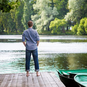 Young handsome man standing on wooden pier, relaxing and meditaing in summer morning, back view — Stock Photo
