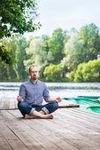 Jonge aantrekkelijke gepaneerd man met gesloten ogen zittend op een houten pier, ontspannen en mediteren in zomerochtend — Stockfoto