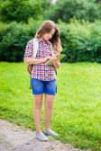 Pretty teenager girl in casual clothes with backpack holding digital tablet in her hand, typing and reading, outdoor portrait — Stock Photo