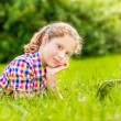 Pretty teenager girl in casual clothes lying on the grass in sunlight with digital tablet or e-book, outdoor portrait — Stock Photo
