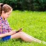 ragazza adolescente bella in casual vestiti seduto sull'erba con tavoletta digitale sulle sue ginocchia, lettura e ritratto di surf, all'aperto — Foto Stock #29969179