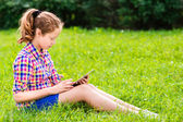 Beautiful teenager girl in casual clothes sitting on the grass with digital tablet on her knees, reading and surfing, outdoor portrait — Stock Photo