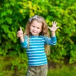 Cute blond little girl with long curly hair showing six fingers (her age) and smiling — Stock Photo
