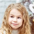 Adorable blond little girl sitting under the Christmas tree and dreaming, closeup portrait — Стоковая фотография