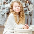 Lovely blond little girl sitting under the Christmas tree with gift box — Stock Photo #36526413