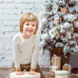 Cute blond little boy sitting under the Christmas tree with gift boxes — Stock Photo