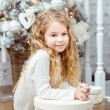 Beautiful blond little girl sitting under the Christmas tree with gift box — Stock Photo #36526419