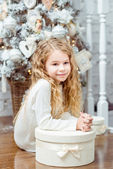 Beautiful blond little girl sitting under the Christmas tree with gift box — Stock Photo