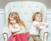 Cute little siblings (boy and girl) being at odds with each other, sitting on armchair — Stock Photo