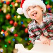 Funny and naughty little boy wearing Santa Claus hat sitting in front of Cristmas tree with colorful lights and putting out his tongue — Stockfoto