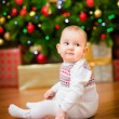 Cute little baby girl sitting in front of Christmas tree with colorful lights and a lot of gift boxes — Stock Photo #37682187