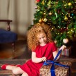 Red-haired little girl sitting on the floor in front of the decorated Christmas tree and unwrapping gift box — Stok fotoğraf #37682191