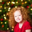 Pretty red-haired little girl wearing red dress sitting in front of Christmas tree with colorful lights — Stock Photo #37682193