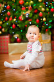 Cute little baby girl sitting in front of Christmas tree with colorful lights and a lot of gift boxes — Stock Photo
