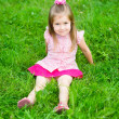 Cute little girl with long blond hair in pink blouse and skirt sitting on grass in summer park, outdoor portrait — 图库照片