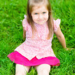 Beautiful little girl with long blond hair, sitting on grass in summer park, outdoor portrait — 图库照片