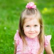 Sweet smiling little girl with long blond hair, sitting on grass in summer park, closeup outdoor portrait — Stock Photo