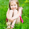 Cute little girl with long blond hair, sitting on grass in summer park putting her hands around her legs, outdoor portrait — Photo