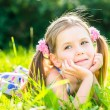 Cute smiling little girl with two blond ponytails laying on grass in summer park, outdoor portrait — Stock Photo