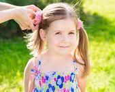 Dulce niña sonriente con su madre las manos haciendo peinado (cola de caballo), retrato de primer plano al aire libre en el parque de verano — Foto de Stock