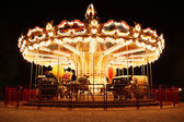 Carousel (Merry-Go-Round) illuminated at night. The picture was taken near Paris, France — Stock Photo