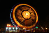 Ferris wheel in motion illuminated at night — Stock Photo
