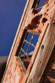 Broken windows and crumbling brick wall at Nevada Ghost town. — Stock Photo