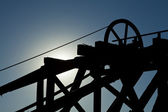 Moonlit Mining hoist and head frame back-lit with blue night sky. — Stock Photo