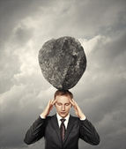 Businessman with stone on his head — Stock Photo