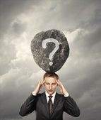Businessman and stone with question on his head on sky background — Stock Photo