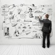 Man drawing strategy on white wall — Stock Photo #24174549