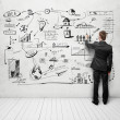 Man drawing strategy on white wall - Stock Photo