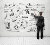 Man drawing strategy on white wall — Stock Photo