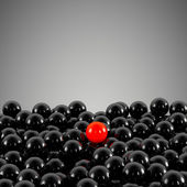 One unique red ball, among other black — Stock Photo