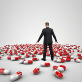 Businessman figure standing in front of heap of red pills — Stock Photo