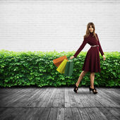 Woman holding shopping bags against wall and bushes — Stock Photo