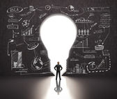 Man in bulb-shaped doorway, business strategy on the wall — Stock Photo