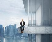Geschäftsmann, sitzen auf dem dach des wolkenkratzers mit kaffee — Stockfoto