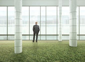 Businessman standing in bright green office — Stock Photo
