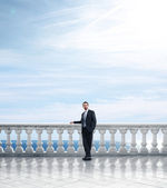 Businessman on column banister — Stock Photo