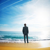 Businessman standing in sea water — Stock Photo